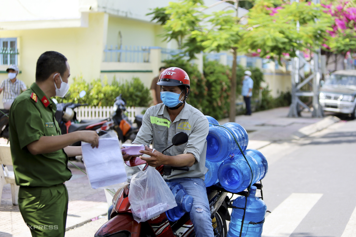 A police officer checks the paper of a water transporter in Loc Tho Ward.Since the seven-day lockdown was imposed, Nha Trang authorities have fined 450 violators a total VND920 million ($40,390).