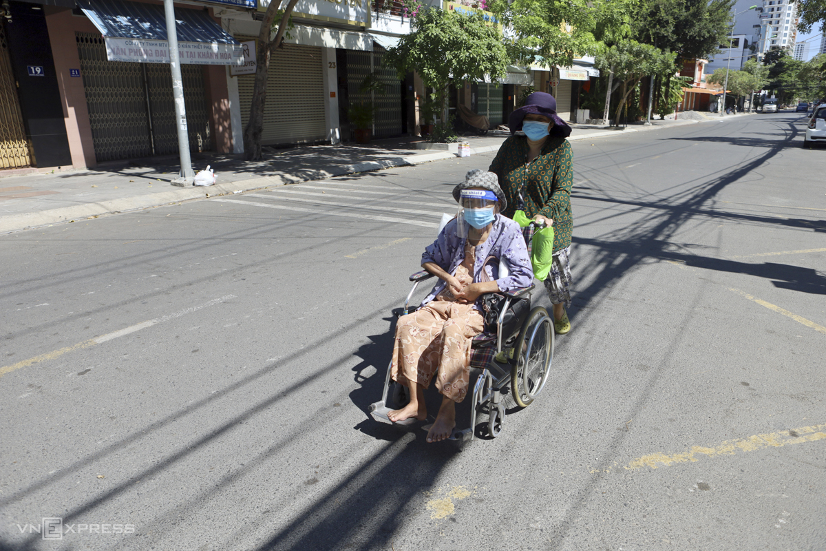 Huu Thi Thuan, 73, is taken home by her niece on Hoang Hoa Tham Street on Tuesday. Thuan must undergo dialysis thrice per week at Khanh Hoa General Hospital in Nha Trang. Her niece said under the new Covid-19 restriction, she could still take Thuan to the hospital for treatment and that all she has to do was present the required papers. However, on Tuesday, there were no staff guarding the checkpoint and I didn't dare go through so I am taking my aunt back home. We will return tomorrow, said the niece.