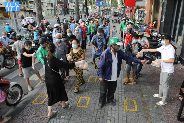 People wait in line for free food in District 1, HCMC, June, 2021. Photo by VnExpress/Quynh Tran.