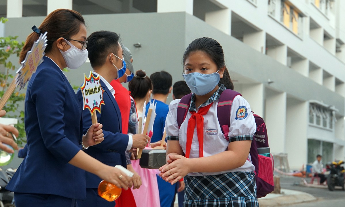 A girl has her hands sanitized upon arriving at a primary school in Go Vap District, HCMC, May 2020. Photo by VnExpress/Manh Tung