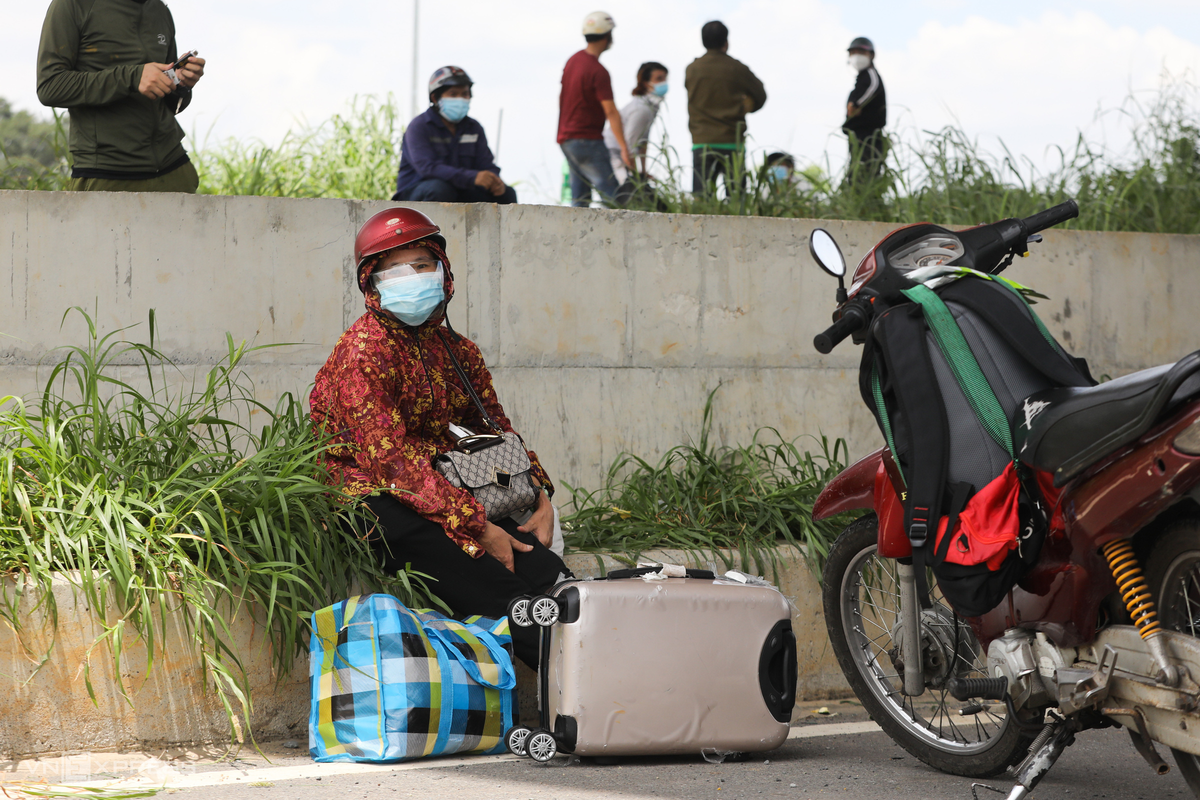A woman waits near a gateway of HCMC as she was stopped from leaving for her hometown in the north central Thanh Hoa Province, August 15, 2021. She worked for a construction site in the city but had been jobless as the site closed due to Covid-19 social distancing order. Photo by VnExpress/Quynh Tran