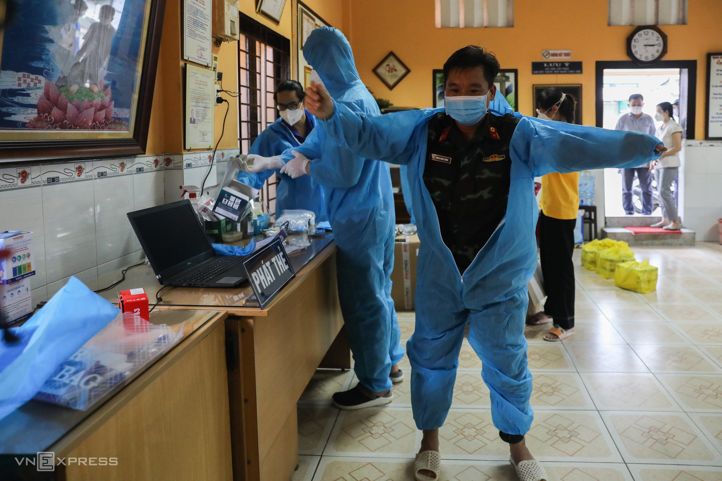 At a mobile medical station in Ward 11 of Binh Thanh District, Doan Ngoc Hung, a doctor from the Vietnam Military Medical University, wears a protective suit on his first day at work in Ho Chi Minh City on Monday.Each mobile medical station has around 4-6 members in charge of management, treating Covid-19 cases at home and vaccinating, among other tasks.