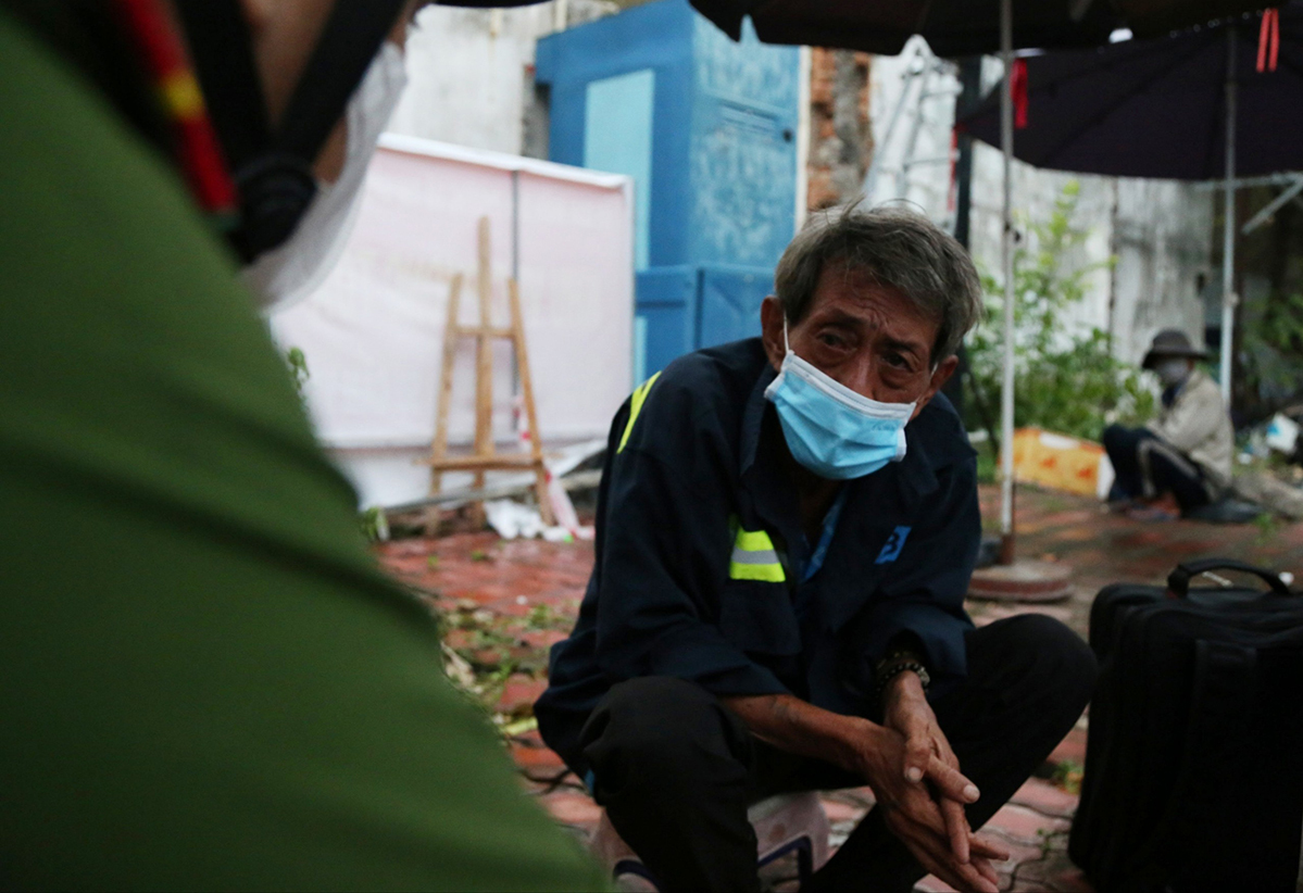 A 65-year-old homeless man on Cach Mang Thang Tam Street in HCMCs District 3 talks to the police, August 24, 2021. Photo by VnExpress/Dinh Van