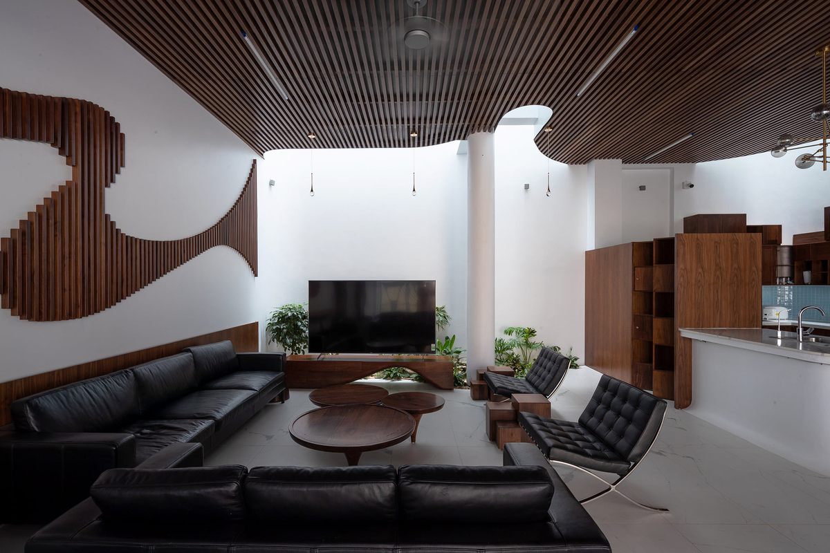 Common spaces like the living room and kitchen are intertwined with greenery, allowing more cool air to be circulated to every part of the house. Dark colors with white and curves help soften the space and bring comfort to residents.