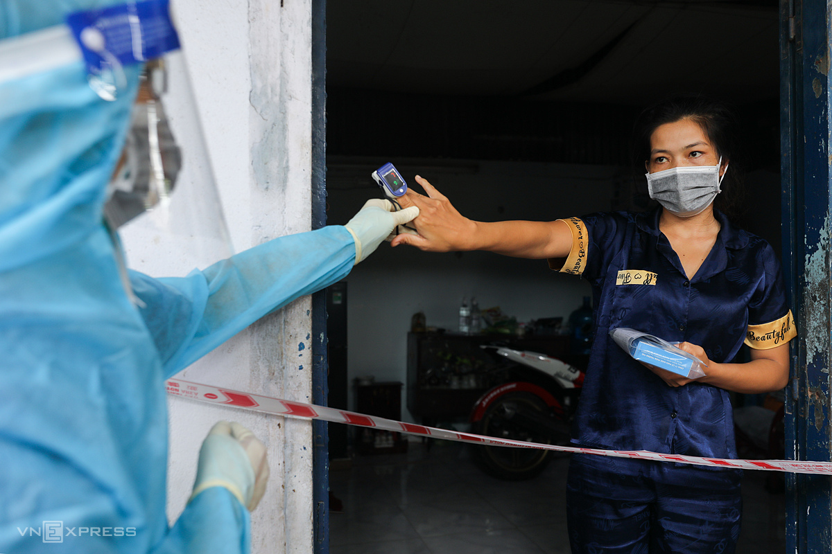 A medic guides a Covid-19 patient to check her blood oxgyen level as Nhân viên y tế phường 3, quận 8, đến thăm khám, đo sPO2, tặng thuốc cho người mắc Covid-19 đang điều trị tại nhà, ngày 29/8. Ảnh:Quỳnh Trần.