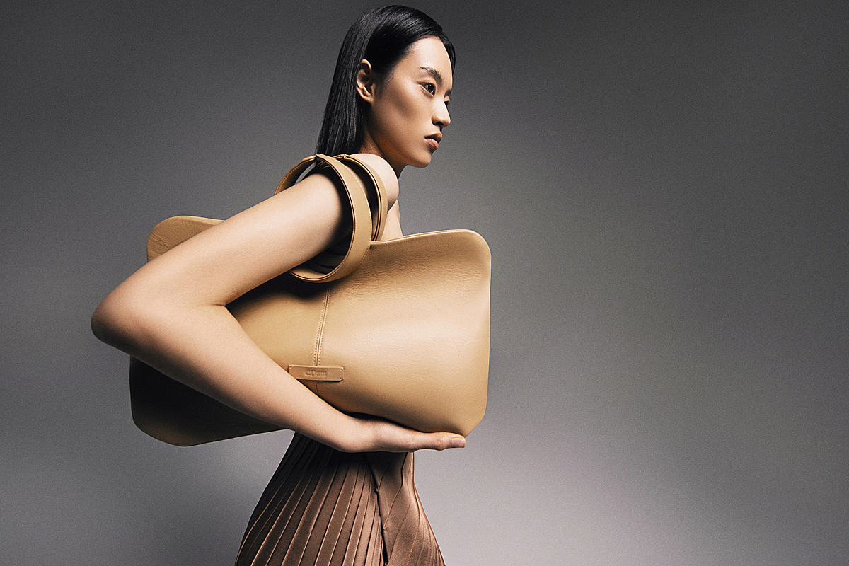 The designer uses geometric elements including triangular and rectangular shapes to seamlessly connect the bag with the bag straps, demonstrating a minimalist style. The bag also has soft rounded lines to create an elegant look.