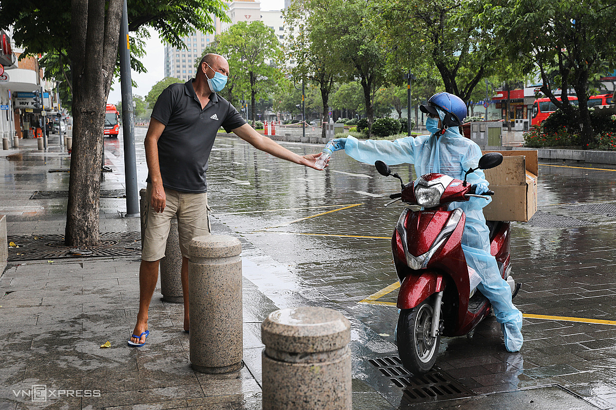 A volunteer hands a free meal and drinking water to a foreinger on Nguyen Hue pedestrian street, August, 2021. Photo by VnExpress/Quynh Tran