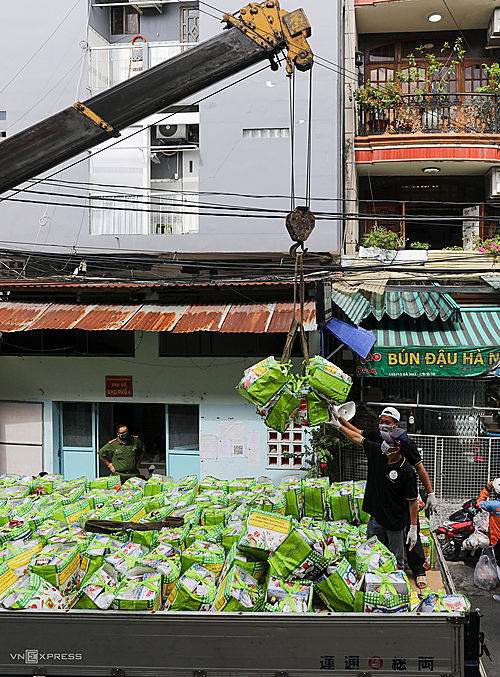 About 20 members of the group were busy hooking gift bags to the crane post. Each time hang about 7 bags of essentials including cooking oil, rice, fish sauce, salt... on hooks to pull up the floors in order from high to low.