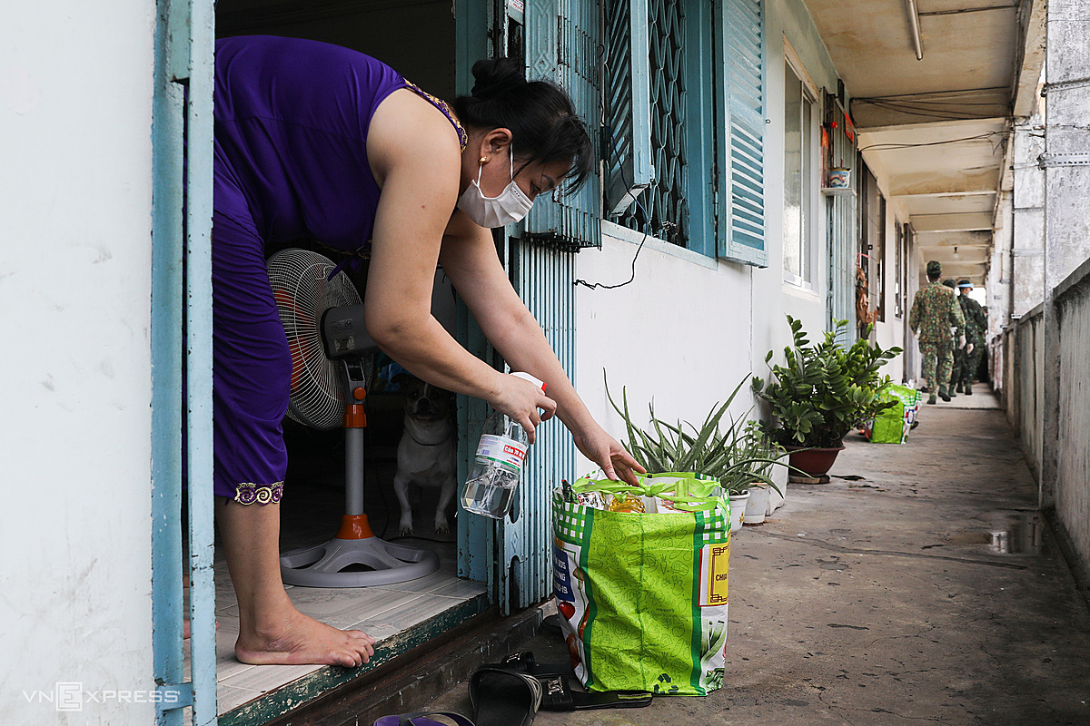 As soon as she received the item, Ms. Duong Thi Minh sprayed disinfectant before bringing it into the house. Distributing food by crane and soldiers delivering it to the door helps us not to go out and limit close contact, she said.