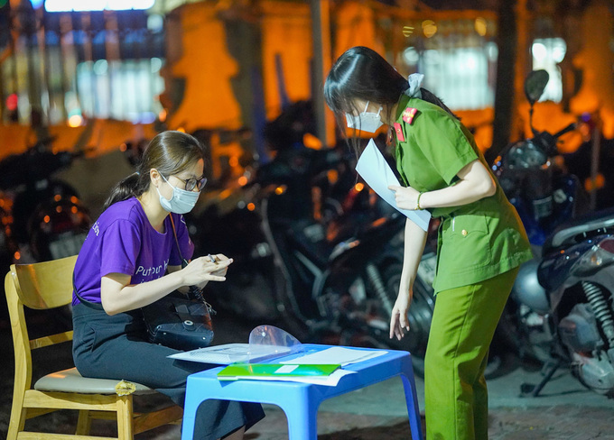 Police guides an applicant to prepare her application. Photo by VnExpress/Pham Chieu
