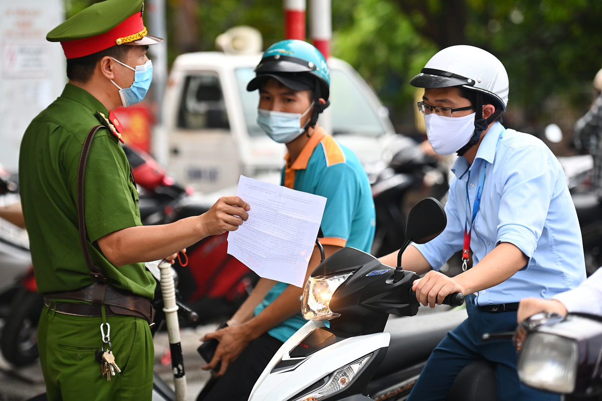 A police officer questions a man over his travel paper in Hanoi, July 28, 2021. Photo by VnExpress/Giang Hy