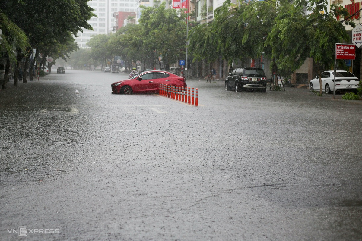 Cars travel from Ly Thai To Street must turn around before reaching Ham Nghi Street. Many motorbikes stop running.  Surrounding streets like Hung Vuong, Quang Dung, and Van Cao face the same flood with water levels up to 50 cm.