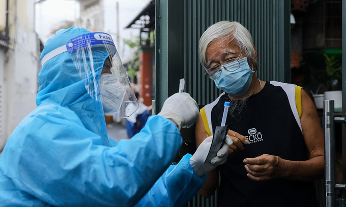 A medic guides a man in HCMCs Binh Thanh District to use a test kit on himself, August 23, 2021. Photo by VnExpress/Quynh Tran
