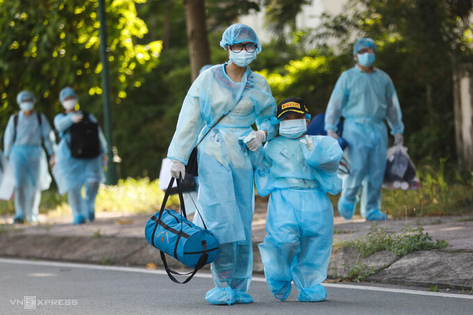 A kis leaves a Covid-19 centralized quarantine facility in HCMCs Thu Duc City in June along with a family member, June 2021. Photo by VnExpress/Huu Khoa