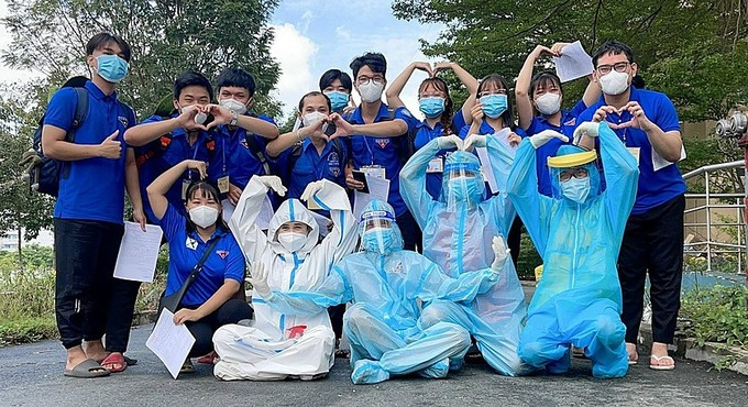 Phuong (wearing white protective clothes) and volunteers in her team. Photo courtesy of Phuong