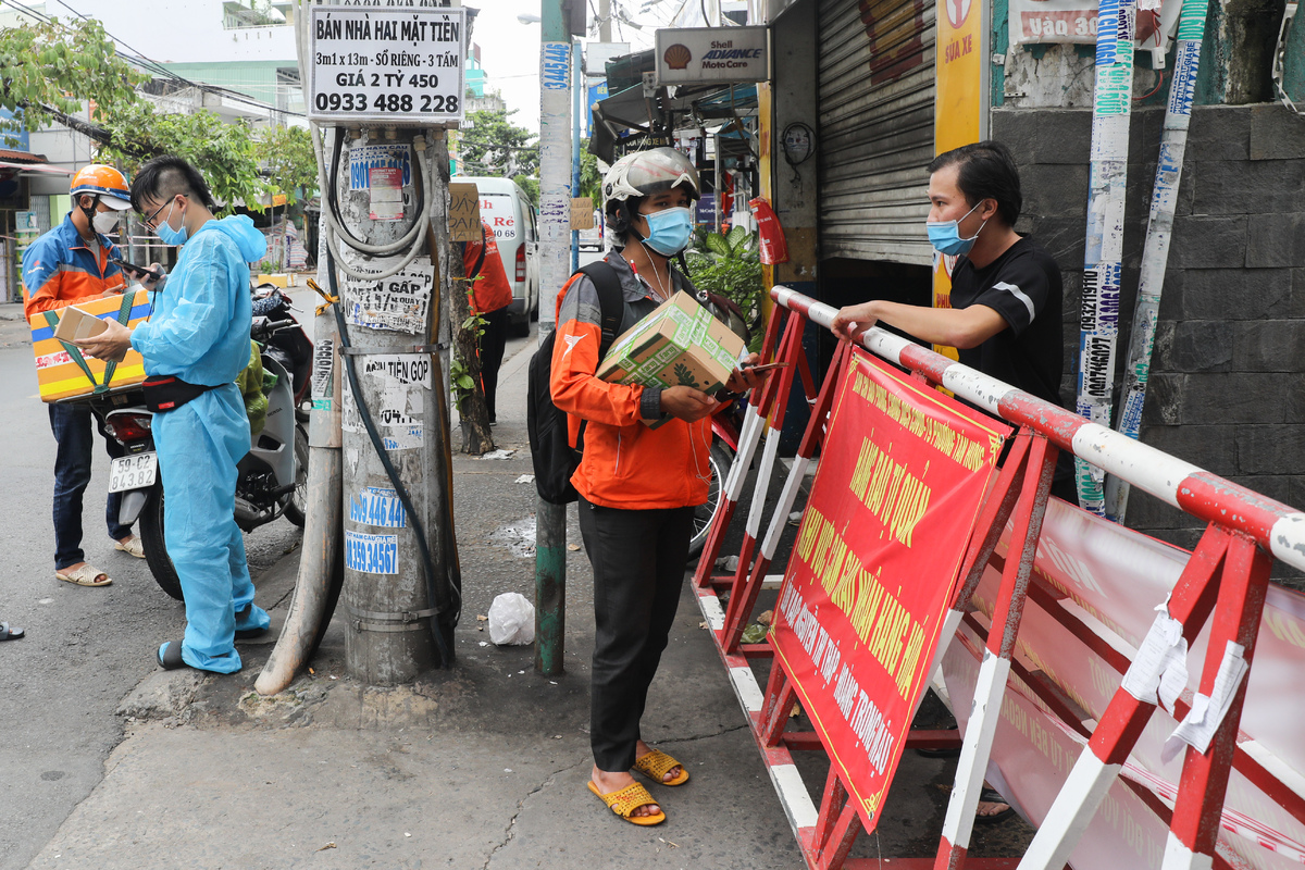 Many streets and alleys are still blocked by barricades. In the photo, delivery workers wait for their recipients at a mouth of an alley on Hoang Trong Mau Street.