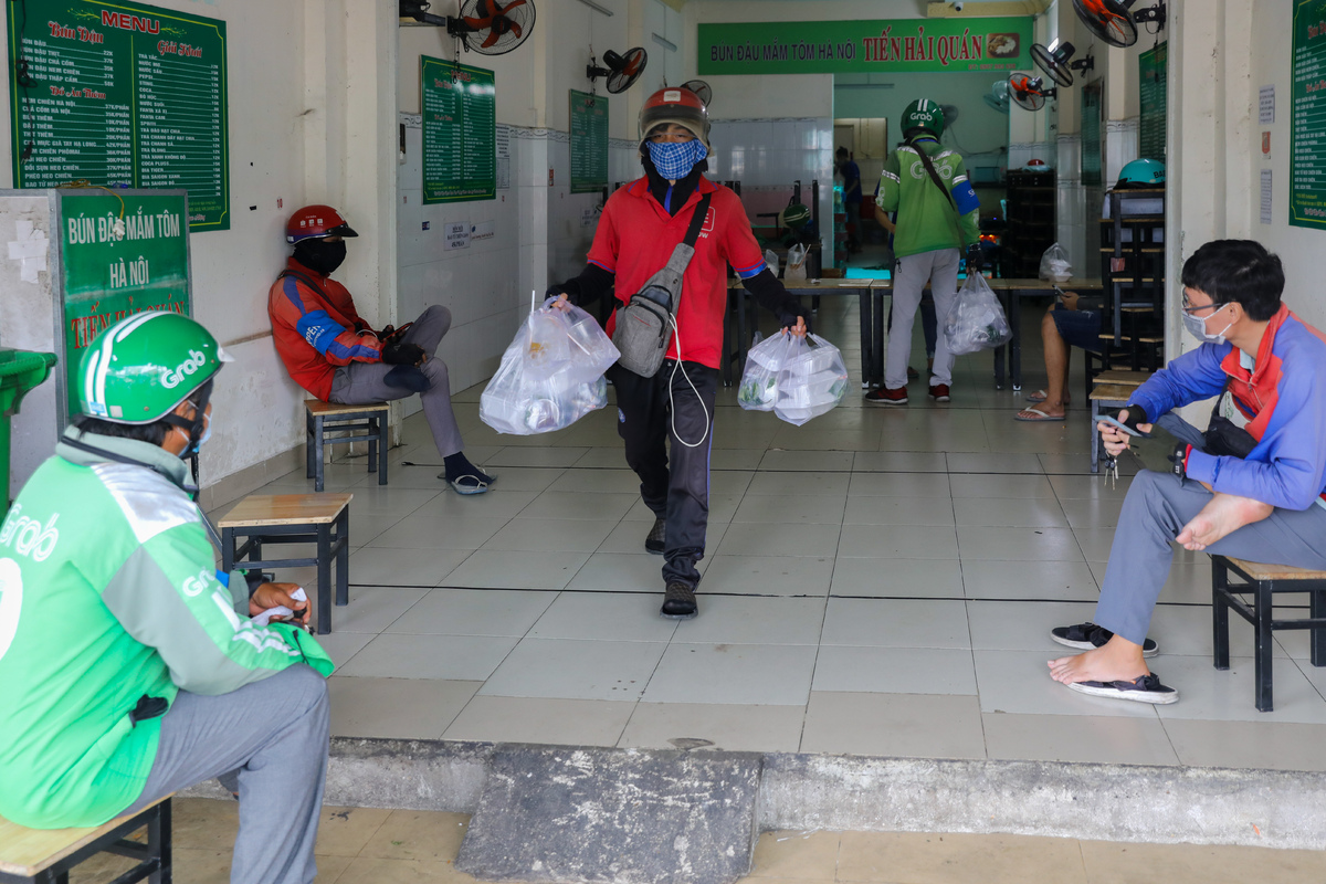 A noodles restaurant on Nguyen Thi Thap Street sees some delivery workers waiting for their patrons' orders.