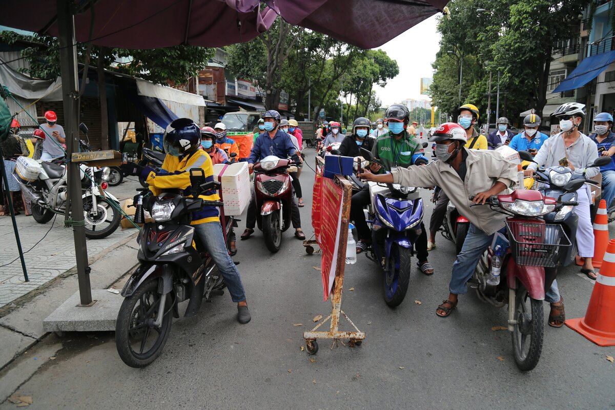 On the first days that delivery workers have been allowed to travel inter-district, many checkpoints are jammed. In the photo, a checkpoint near Ben Xe Mien Dong (Eastern Region Bus Station) in Binh Thanh District is filled with motorbikes. It takes people up to ten minutes to have their QR code scanned by two scanners.