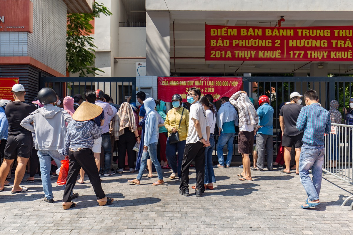 To mandate social distancing rules, Thuy Khue Ward's People's Committee set up mobile stalls at Chu Van An Primary School for locals to buy mooncakes supplied by traditional bakeries, attracting thousands of patrons and causing mayhem days before the Mid-Autumn Festival on Sept. 21.