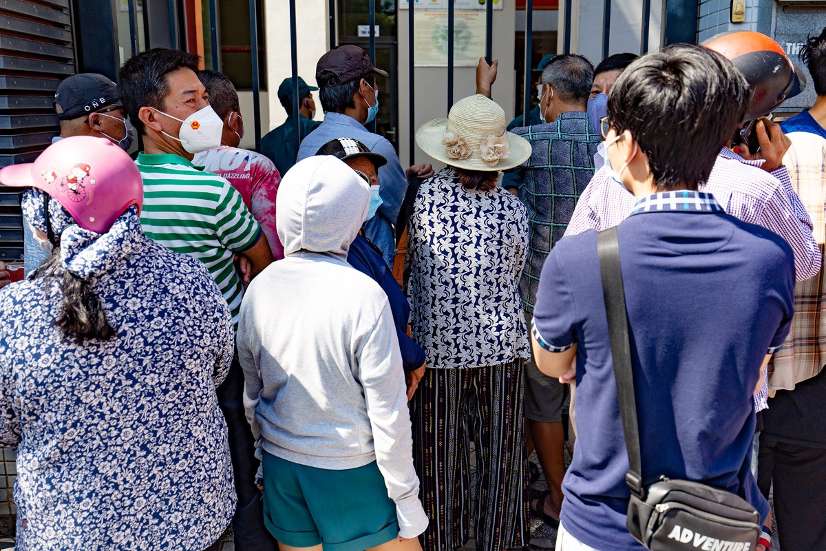 At 1:20 p.m. Sunday, many people wait outside the school even though the stalls are not open.