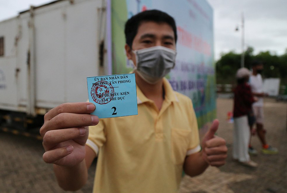 A man shows his approved document to enter Canh Doi Park in District 7, HCMC, after the city pilots outdoor exercise as another step to lift Covid restrictions, Sept. 21, 2021. Photo by VnExpress/Dinh Van