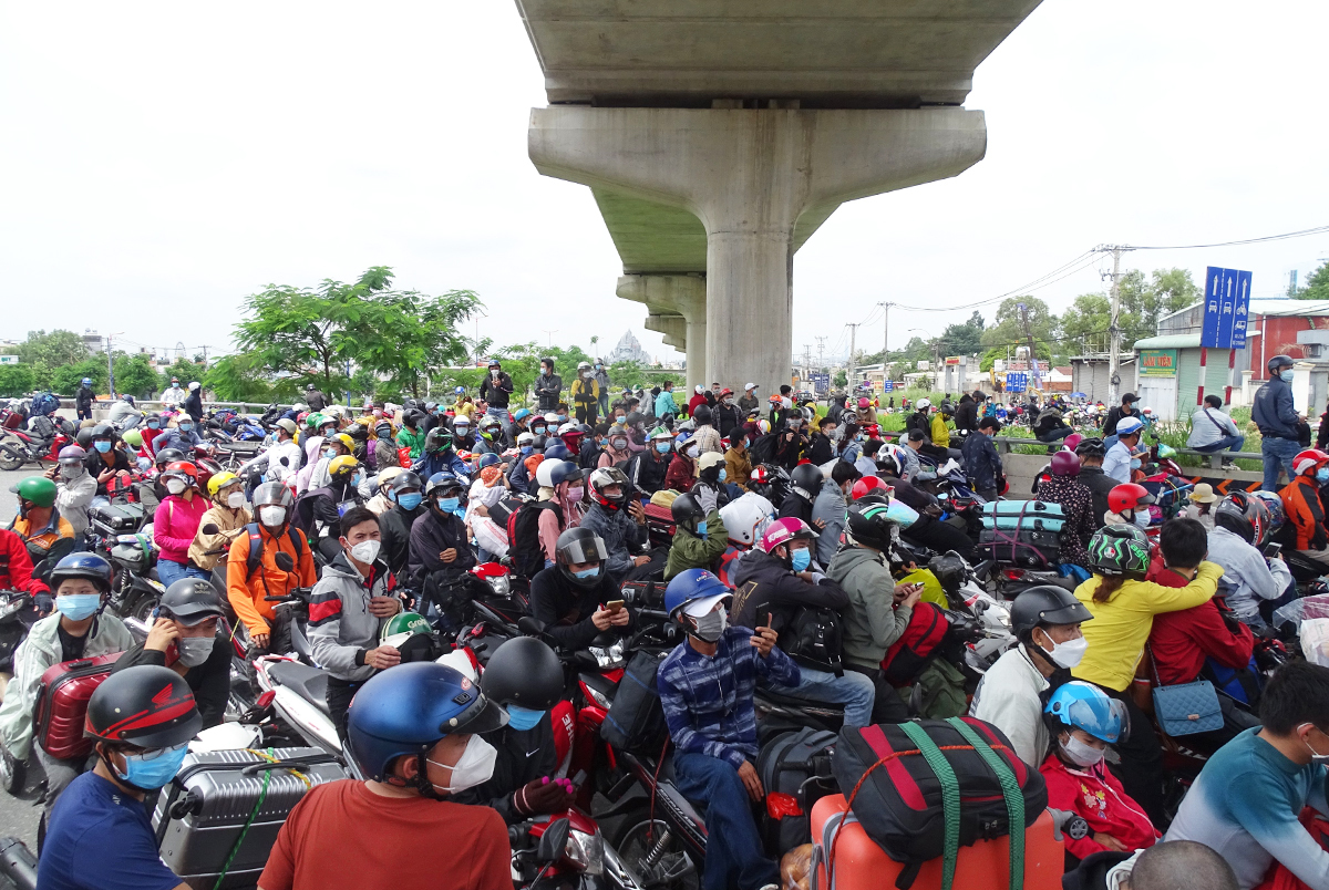 A large crowd of migrants gathers at a checkpoint near HCMCs Suoi Tien Park on the Hanoi Highway to return to their hometowns, Aug. 2021. Photo by VnExpress/Ha An