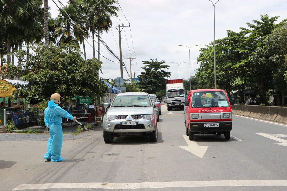A traffic police officer stop vehicles for a random check in Cu Chi District, September 22, 2021. Photo by VnExpress/Ha Giang