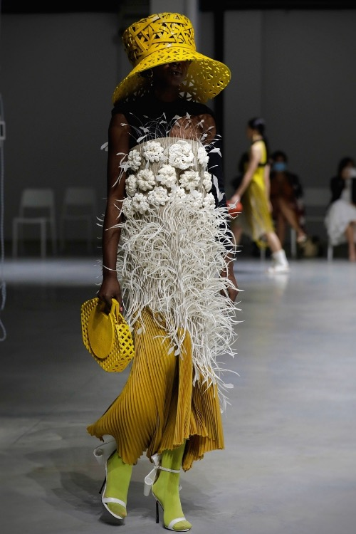 The shirt is adorned with flowers and feathers, combining with pleated trousers. The yellow floppy hat is inspired by Vietnamese bamboo baskets.