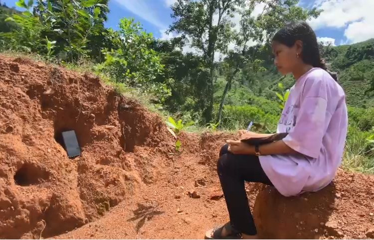 Dinh Thi Tiep attends an online class up on a hill. Photo by VnExpress/Thuong Hoang