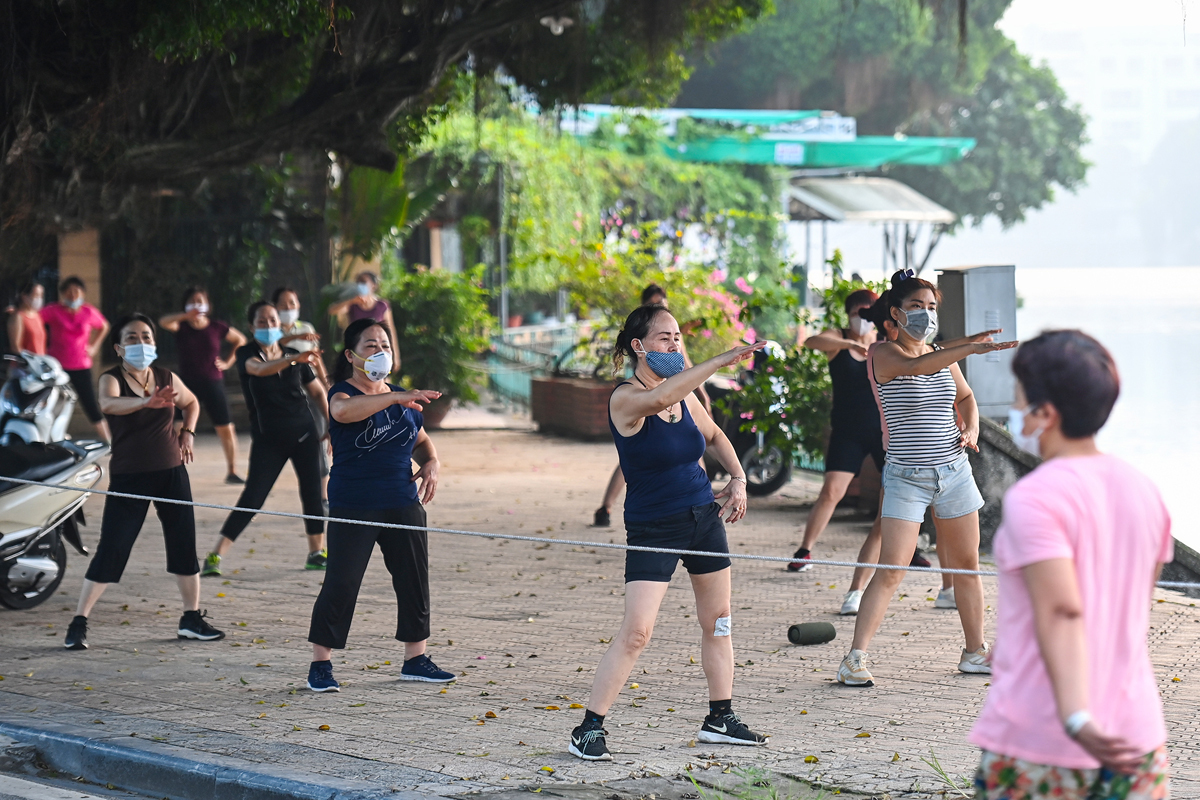 A group exercises to music and has a coach on the sidewalk of Thanh Nien street, on the side of Truc Bach lake.