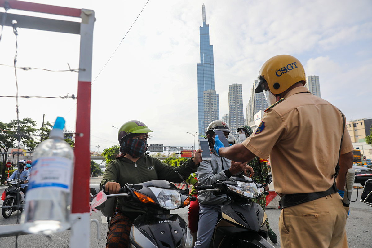 A police officer scans a QR code to check if a woman is out on the street in line with HCMCs rule on social distancing, August 2021. Photo by VnExpress/Quynh Tran