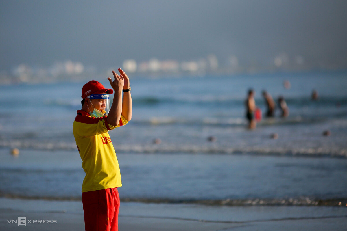 A rescuer blows his whistle to tell people to stop swimming at 6:30 a.m.