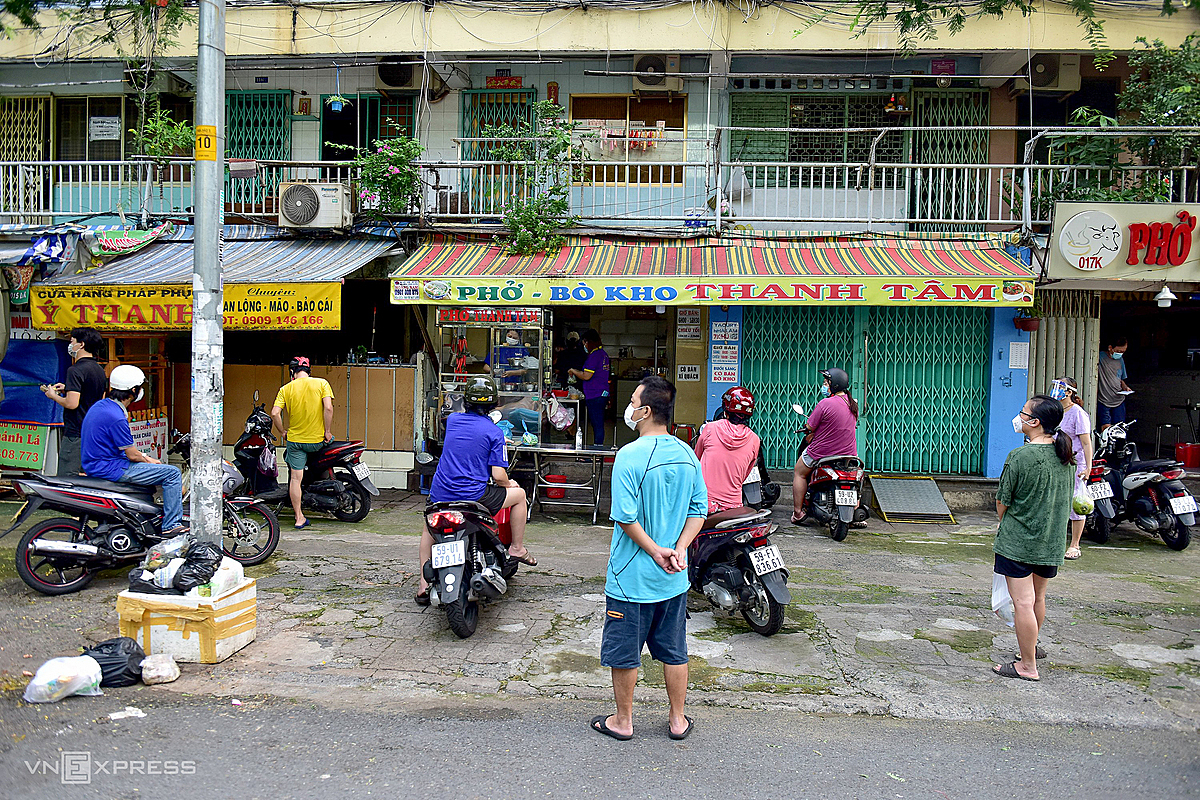 People obey to stand 1.5m apart in front of a noodle shop, braised beef on Su Van Hanh Street (District 10).
