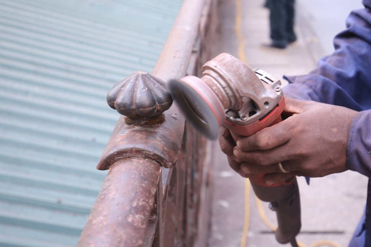 Workers clean the railings before applying anti-rust paint, and another two layers of paint afterwards.
