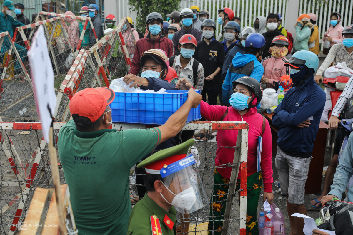 Huynh brought a basket of food, standing close to the barriers and giving them to others.I told people in my groups to cook hundreds of portions, but the number of the needy is too high, I cannot help them all.