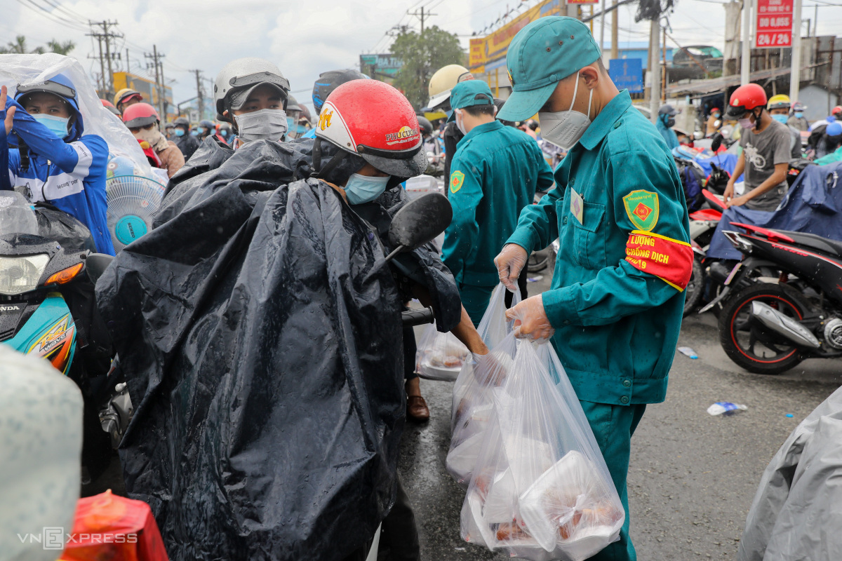 Local security forces in Tan Tuc Town of Binh Chanh District took turns to give away meals, bread and milk.