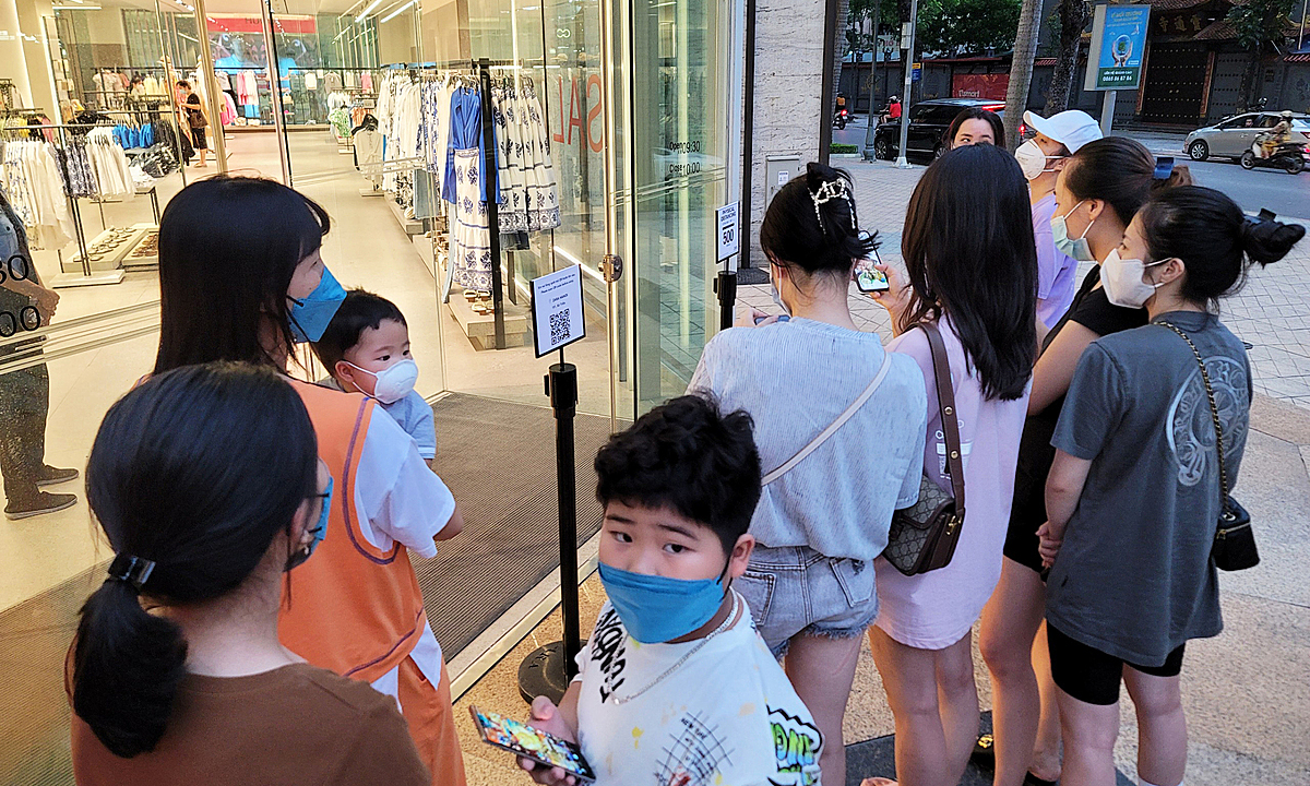 Customers queue up out side the store of fashion brand Zara store. To avoid crowds, the store only allows five customers to enter each time.