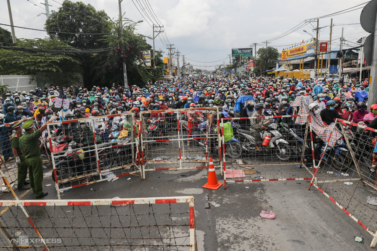Thousands of people in HCMC carrying their belongings and children took to the National Highway 1 to return to their hometown return to their hometowns in the Mekong Delta by motorbike on Oct. 1, 2021. Photo by VnExpress/Quynh Tran