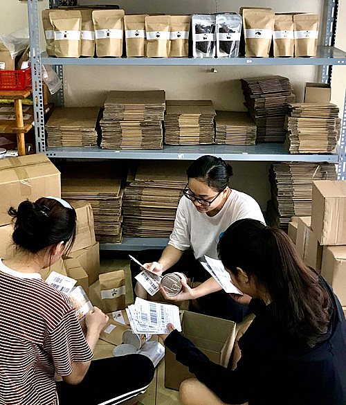 Oanh (middle) and two employees are packing goods before shipping to customers, June 2021. Photo courtesy of Oanh