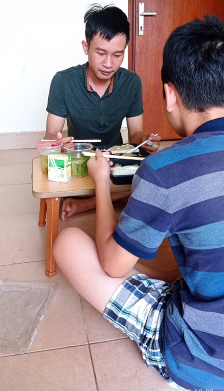 Nguyen Van Phong and his younger brother eat lunch at an isolated place in the dormitory of FPT University, on September 6, 2021. Photo courtesy of Phong