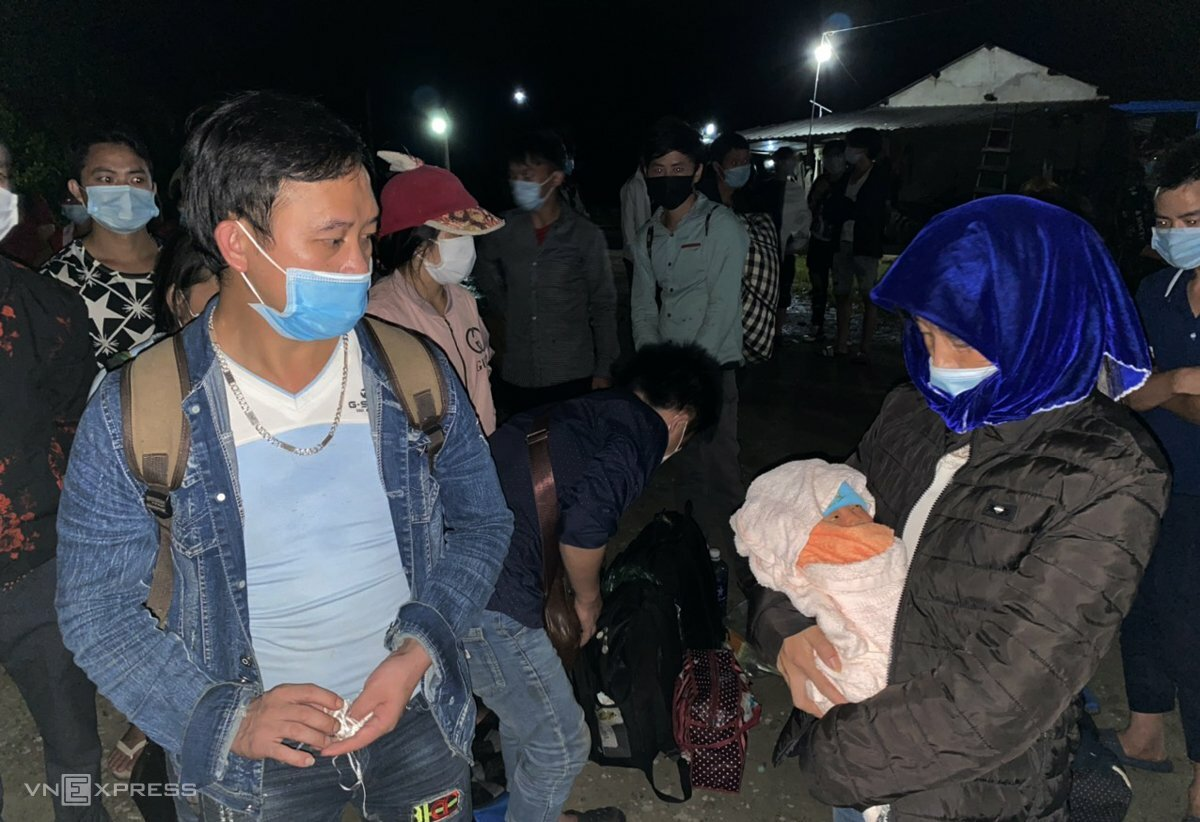 Giang Minh Xa and his wife Song Thi Say, who is holding their baby, are on their trip to return home, October 4, 2021. Photo by VnExpress/Dac Thanh