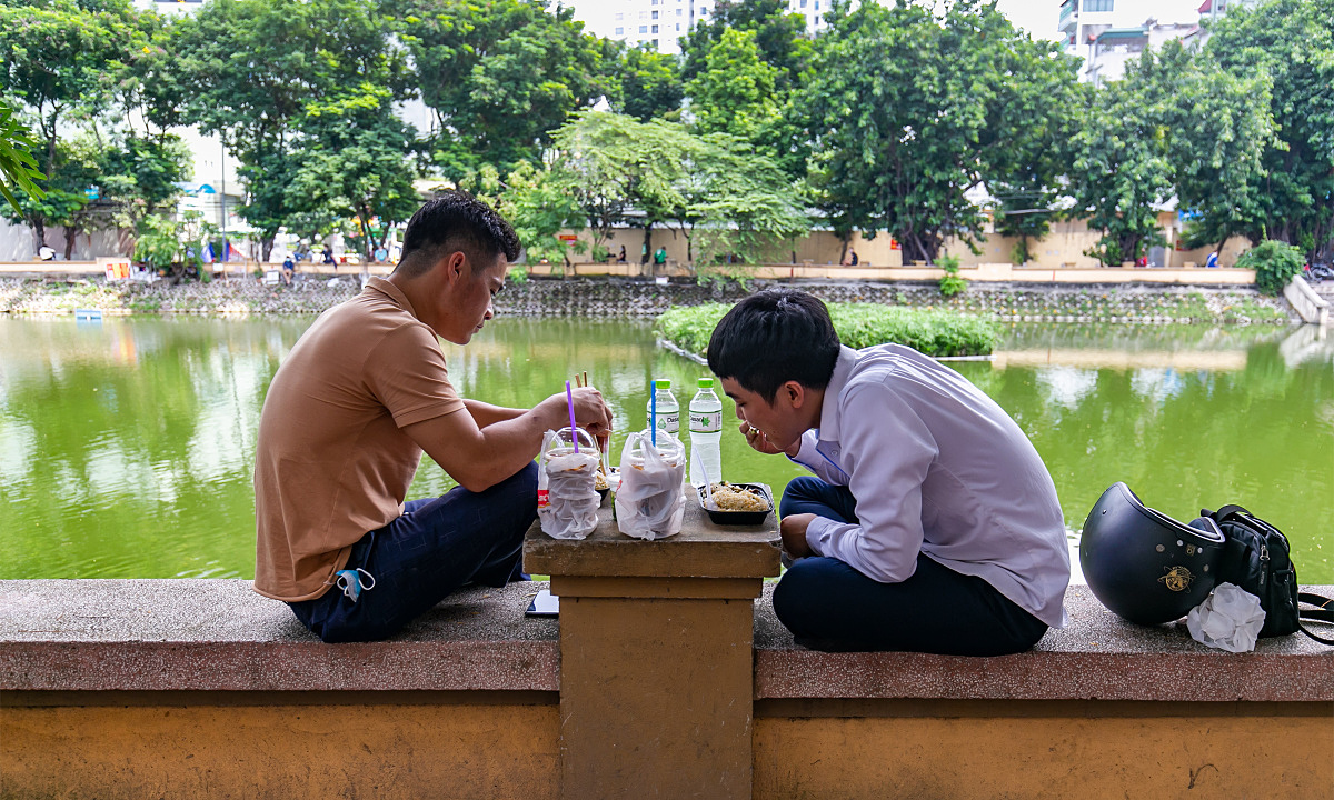 Two men had lunch by Lang Thuong Lake in Dong Da District, Oct. 5, 2021.  Hanoi eateries have been allowed to reopen for takeout and deliveries, so many people have used public spaces to enjoy their daily meals.