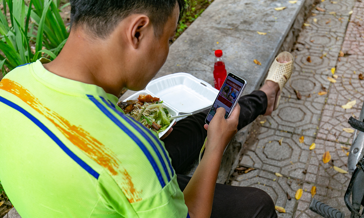 A man surfed the web while having lunch, saying it is uncomfortable and unhygienic to eat on a sidewalk like this.