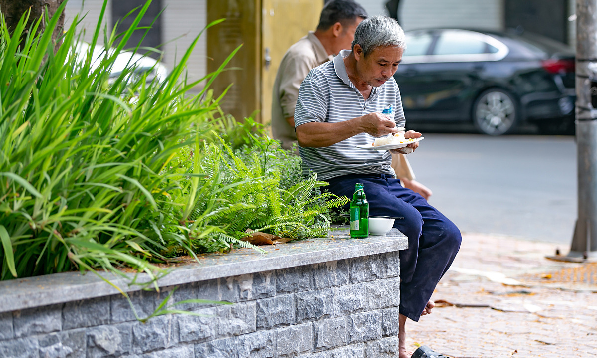Delivery workers and people working outdoors choose wherever they can have a seat to have their meals.