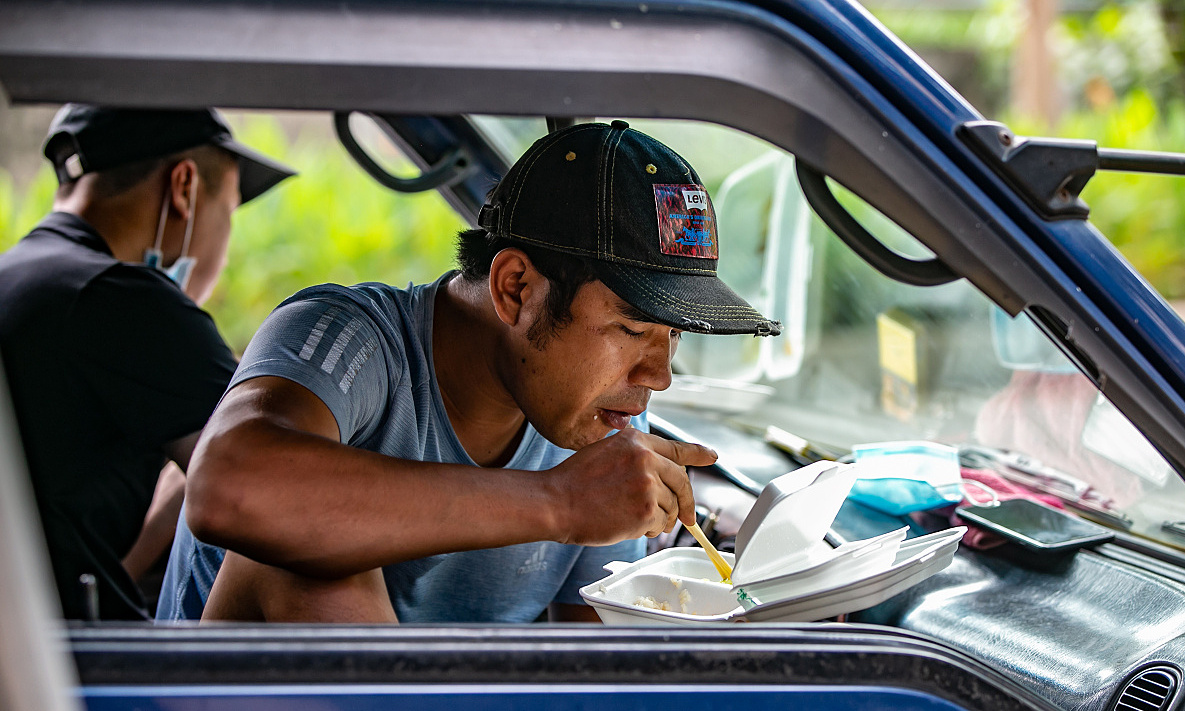 A man had his lunch in a truck before resuming work in the afternoon.