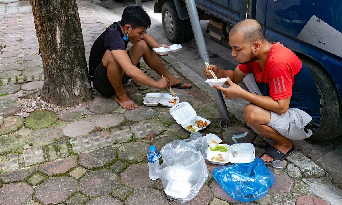 Vu Van Tien (R), employee of a delivery firms, had his lunch under a shade of a tree on Oct. 5 2021.