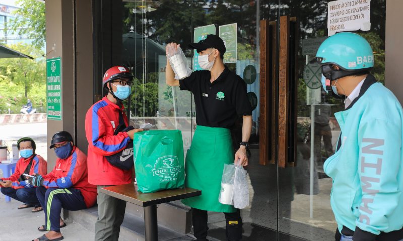 Shippers wait to pick up orders at a coffee shop in Ho Chi Minh City on September 16, 2021. Photo by VnExpress/Quynh Tran