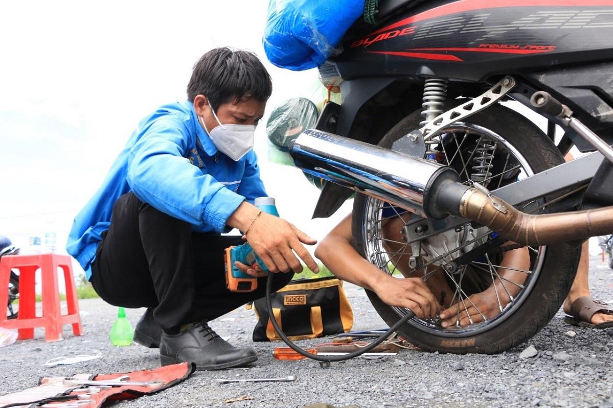 Han and team members help people repair motorbike with punctured tires on National Highway N2 in September 2021. Photo courtesy of Han