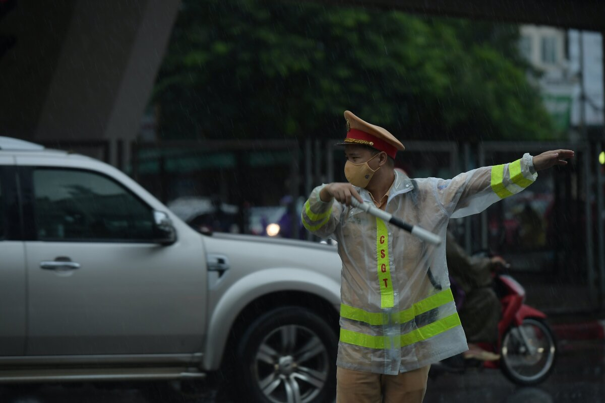Traffic police worked under the morning rain to direct vehicles.