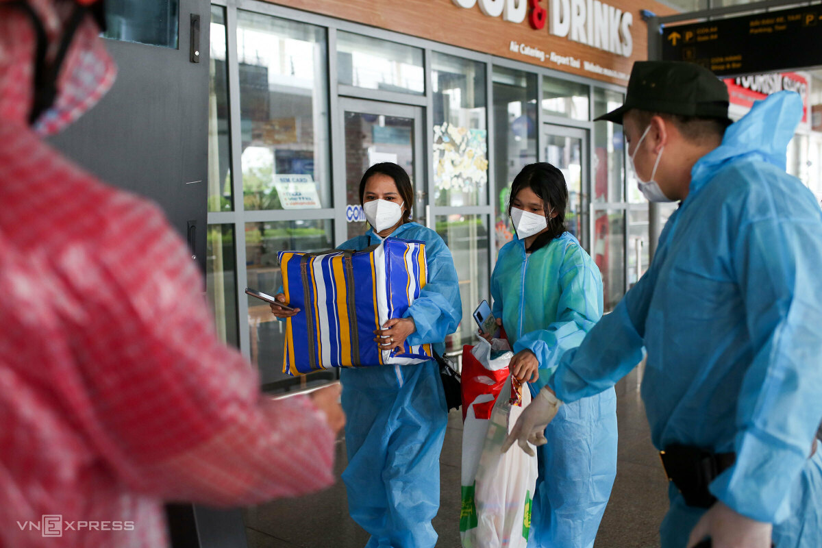On Oct. 12, two flights from HCMC landed in central Da Nang City. In the photo, Dang Thi Thu Thanh, 33, and her daughter Le Viet Thuy Linh, 12, residents of Da Nang's Thanh Khe District, handed the funerary urns of Dang Thi Ai to her brother, also Thanh's father, Dang Van Nam, 62.  Ai, 59, died of Covid on Sep. 14. Thanh has had only one dose of vaccine, so she must be in centralized quarantine after giving the urn to her father.  Thanh was a worker at a garment factory in HCMC, her daughter visited her in June for her summer vacation, and the duo stayed in our room all days, having fried rice and instant noodles in four months.  Tran Hung Phong, vice chairman of Da Nang Fellows Association in HCMC, helps us with the quarantine fee and procedure to bring the urn on this repatriation flight, Thanh said.